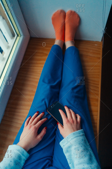 Faceless woman in comfy home clothes and socks sitting on window sill at home holding mobile phone