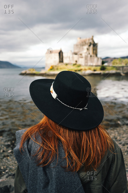 Back view of stylish woman wearing a hat contemplating old stone castle on coast in mountains, Scotland