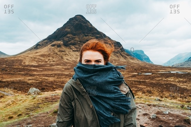 Beautiful ginger woman swaddled in scarf standing against picturesque mountains of Scotland