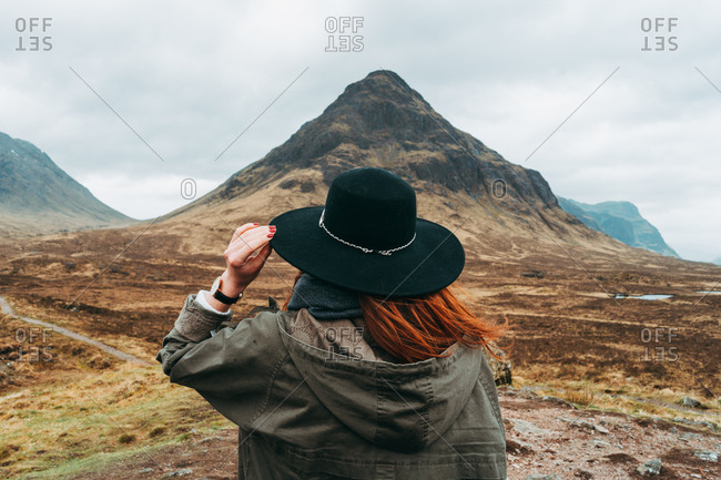 Unrecognizable ginger woman wearing and holding hat standing against picturesque mountains of Scotland