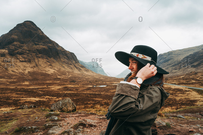 Beautiful ginger woman wearing and holding hat standing against picturesque mountains of Scotland