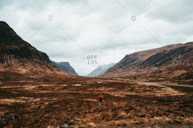 Unrecognizable person wearing red coat walking through picturesque mountains of Scotland