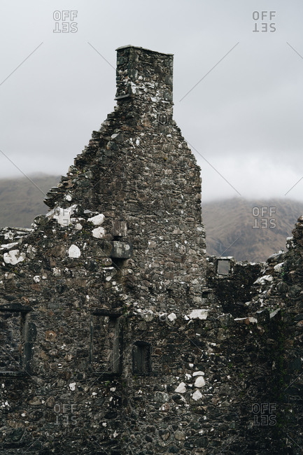Aged medieval stone building with mountains behind it covered in fog, Scotland
