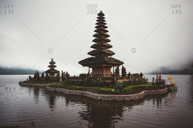 June 25, 2019: Small complex of prayer pagoda with green garden around built in water on shore against fog, Bali