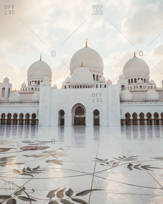 February 21, 2019: Beautiful white mosque with domes and minarets under bright blue sky, Dubai