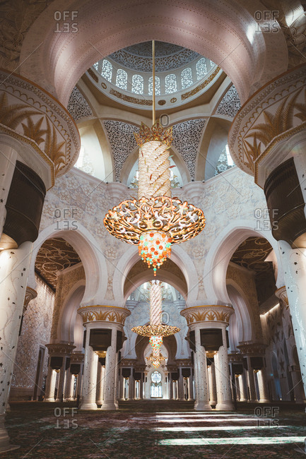June 25, 2019: From below view of mosque interior with glowing golden lamp and ornamental columns, Dubai