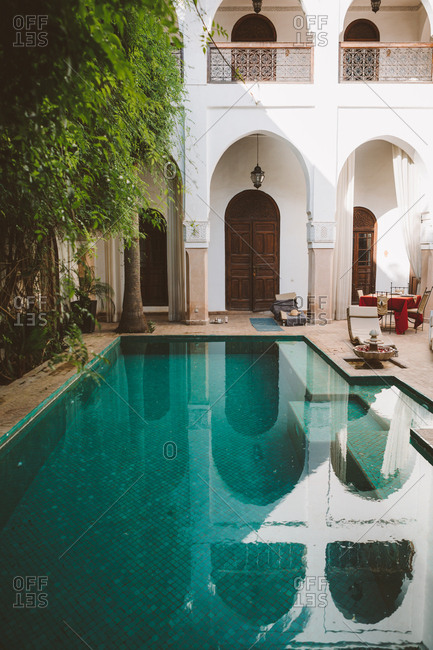 June 25, 2019: Peaceful clear water of pool on terrace of exotic resort with oriental architecture in sunlight, Morocco