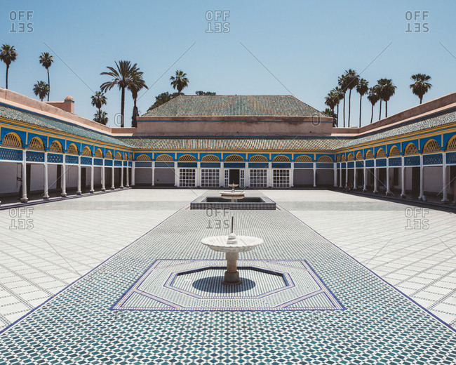 June 25, 2019: Patio with colorful tiled floor and fountains surrounded with covered gallery and pillars in oriental style, Marocco