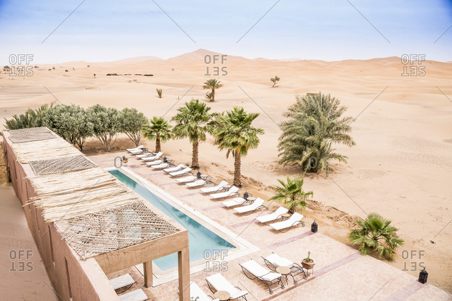 June 25, 2019: From above of stone terrace with pool and sunbeds among rare palms in desert sand, Morocco