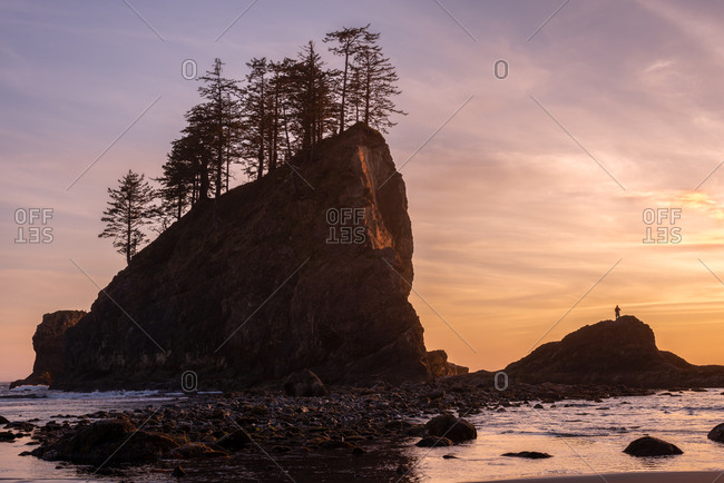 Sea stacks with low tide at sunset with human silhouette