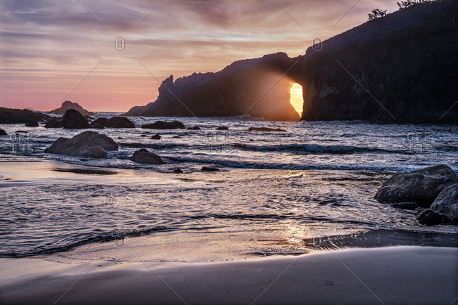 Sunlight passing through hole in a cliff at sunset