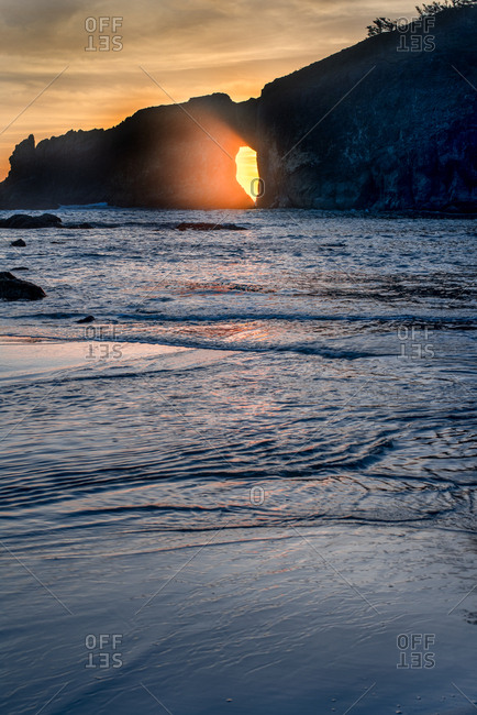 Sunlight passing through hole in a cliff at sundown