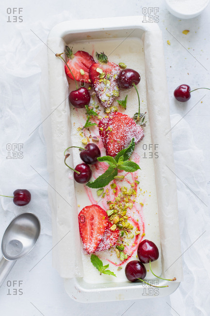 Overhead view of strawberry vanilla ice cream with pistachios, cherries and mint