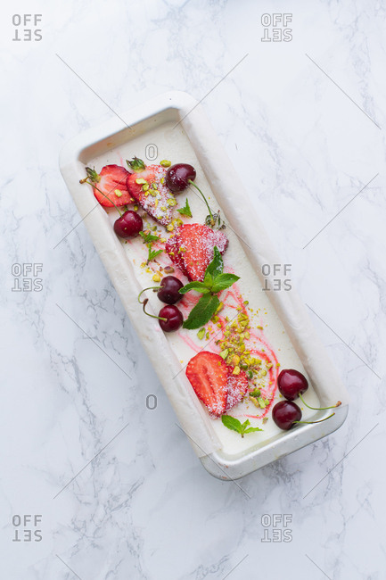 Strawberry vanilla ice cream with cherries, pistachios and mint