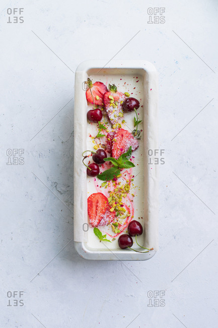 Overhead view of strawberry vanilla ice cream with cherries, pistachios and mint