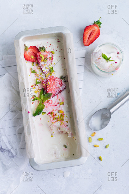 Strawberry vanilla ice cream with pistachios and mint being served