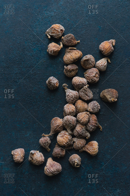 Overhead view image of dried mini figs on blue background