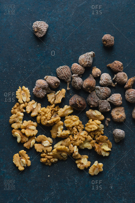 Dried walnuts and small figs on blue background