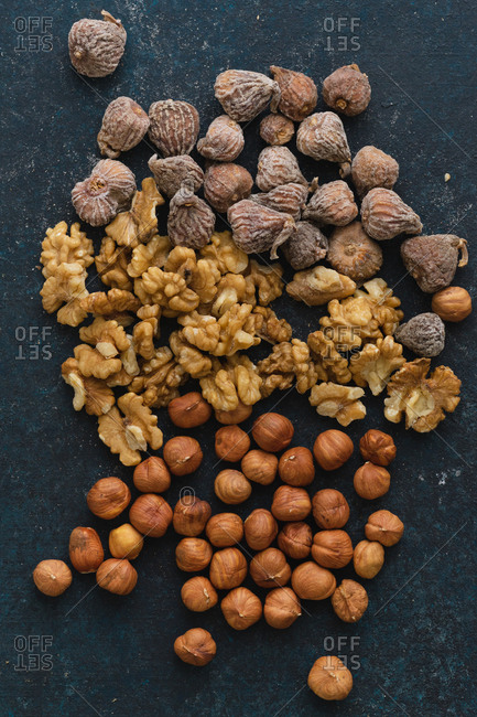 Flat lay with various nuts and dried fruits: hazelnuts, walnuts and figs