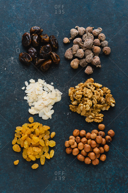 Flat lay with various nuts and dried fruits: hazelnuts, walnuts, raisins