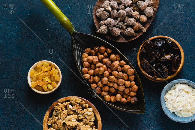 Bowls filled with various nuts and dried fruits: hazelnuts, walnuts, raisins
