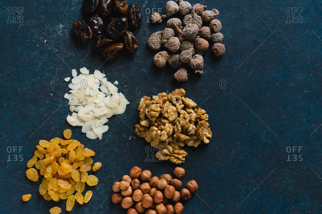 Various nuts and dried fruits: hazelnuts, walnuts, raisins on dark blue background