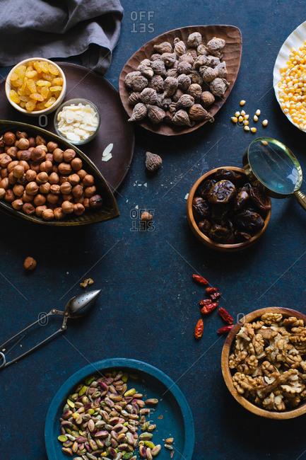 Various nuts and dried fruits: hazelnuts, walnuts, raisins on dark background