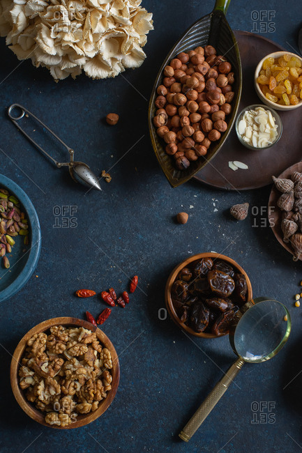 Overhead view of various nuts and dried fruits: hazelnuts, walnuts, raisins