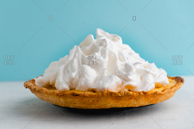 Sweet cake with lemon curd and Italian meringue against blue background