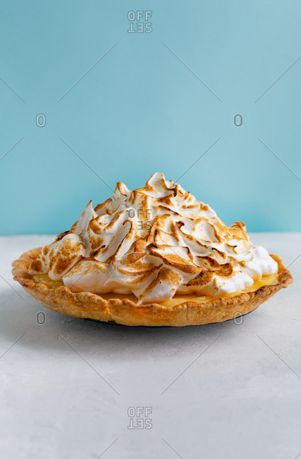 Sweet cake with lemon curd and toasted Italian meringue against blue background