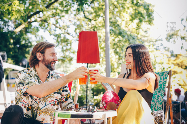 Authentic image, happy couple in love having beer outside. Attractive man and beautiful young woman saying cheers. Summer music festival atmosphere.