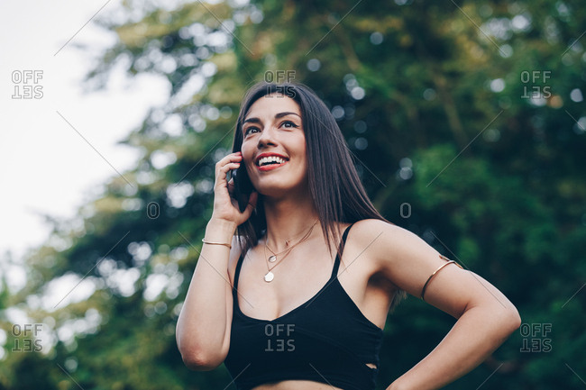 Portrait of a beautiful young woman talking on her smartphone on a summer day outdoors