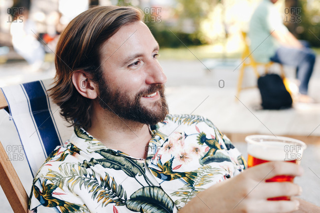 Candid portrait of attractive man in his thirties toasting to his girlfriend with beer on a date on a summer day outdoors.
