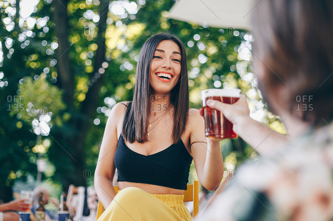 Candid portrait of beautiful young woman toasting to her boyfriend with beer on a summer day outdoors.