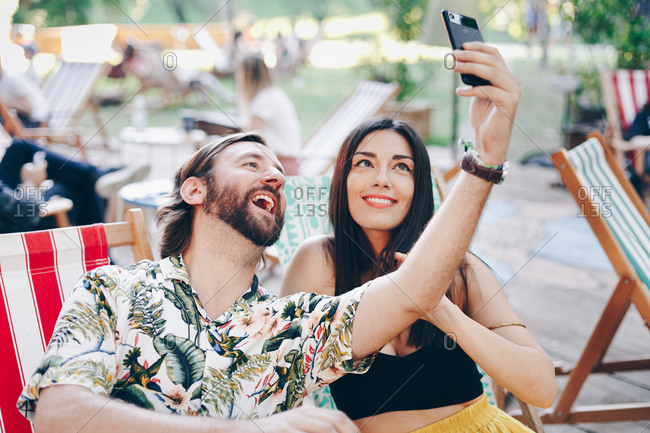 Beautiful happy couple in love taking a fun selfie outdoors on a summer day.