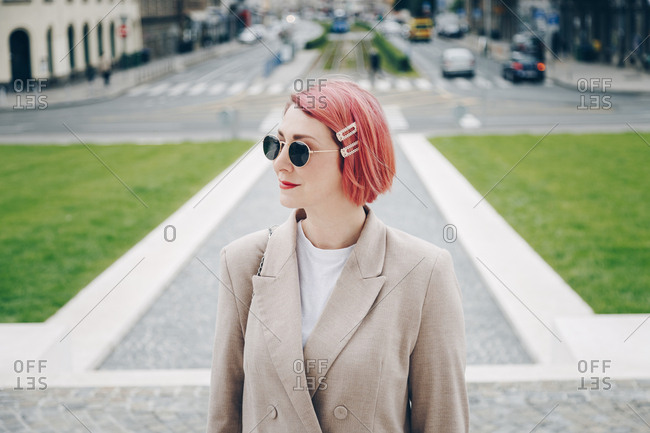 Streetstyle portrait of a beautiful fashionable woman with pink hair wearing sunglasses and oversized blazer in the city