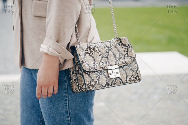 Streetstyle close up of a trendy snake skin purse. Fashionable woman holding a stylish bag in the city, wearing an oversized blazer