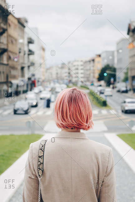 Rear view of a fashionable woman with pink hair oversized blazer in the city, european streetstyle