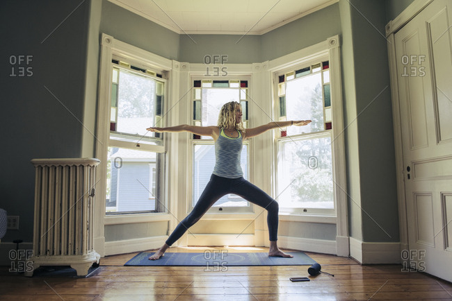 Young woman practicing yoga on exercise mat against window