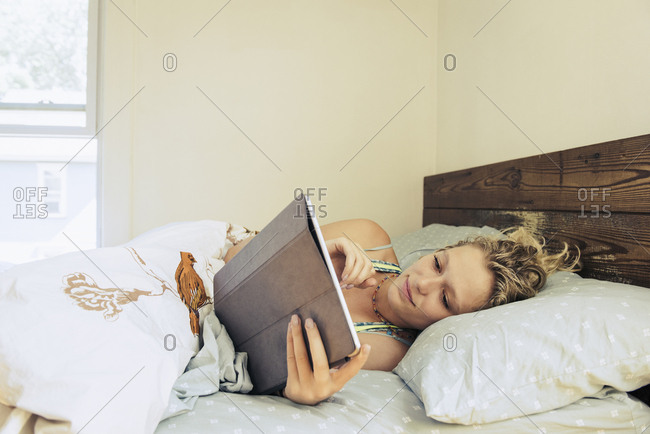 Young woman using digital tablet on bed at home
