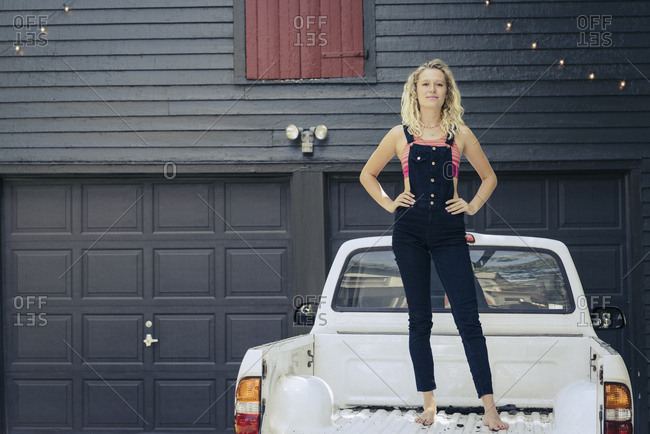 Portrait of young woman standing on pickup truck against house