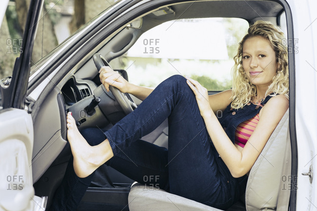 Full length portrait of smiling young woman sitting in pickup truck