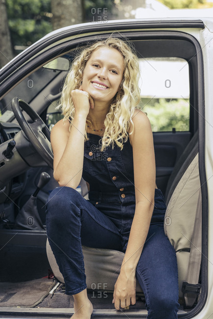 Portrait of smiling young blond woman sitting in pickup truck