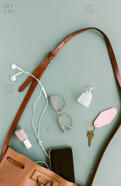 Contents of a woman's purse spilling out on a light green background