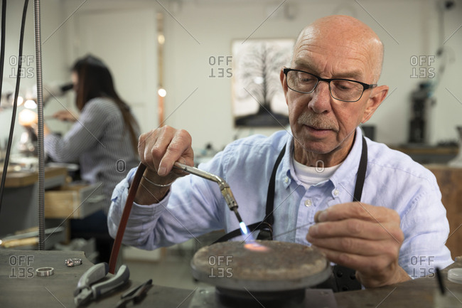 Confident senior male jeweler using blow torch at workshop