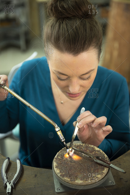 Confident young female jeweler using blow torch for molding ring at workshop