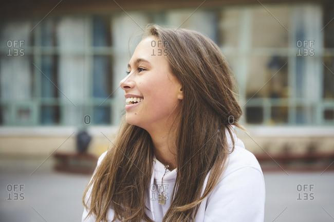 Smiling teenage girl looking away while sitting in schoolyard