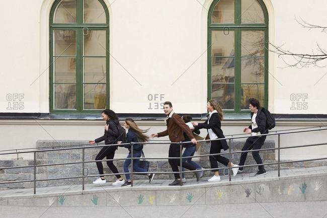Cheerful teenage girls and boys running on walkway of high school