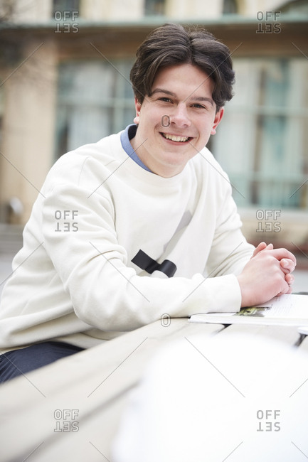 Portrait of confident teenage boy sitting at table in schoolyard