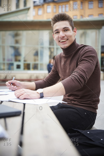 Portrait of teenage boy smiling while sitting at table in schoolyard